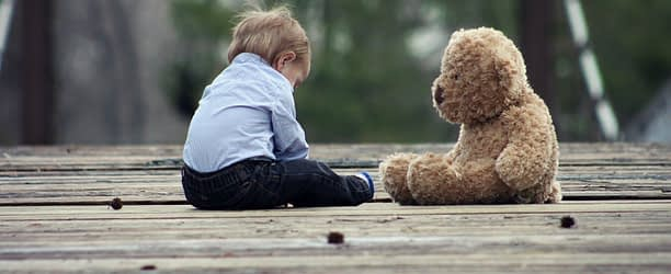 Baby and Toy sitting on wooden floor