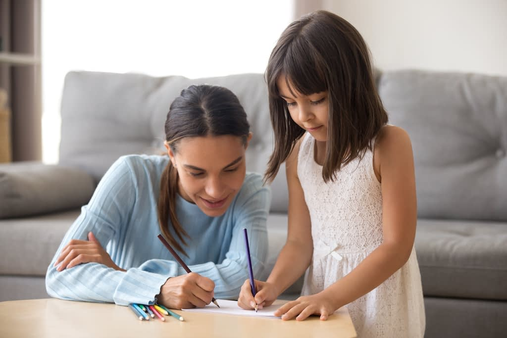 woman and little girl are drawing together at home