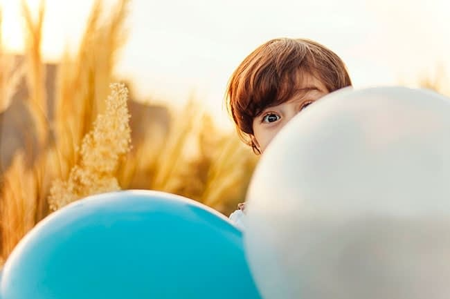 Boy is hiding behind a ballon